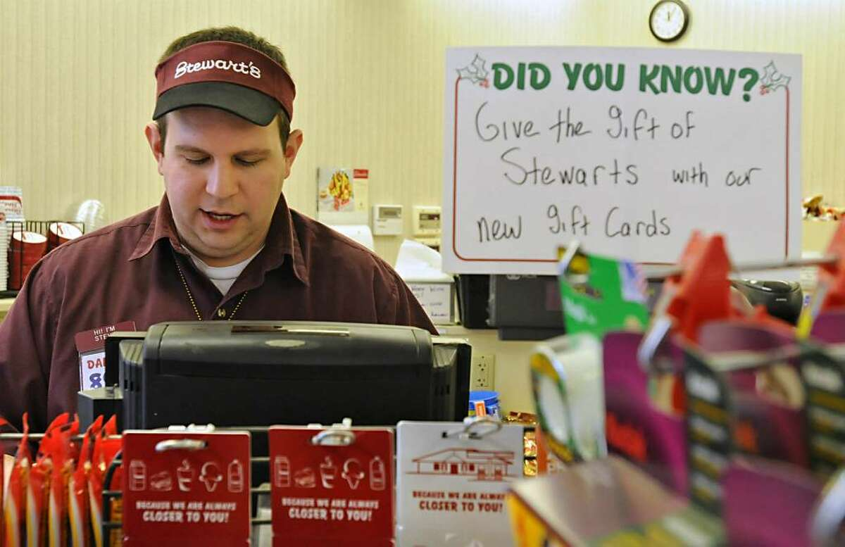 Christmas Day is a busy day for Stewart?s Shop store manager Steve Babin in Clifton Park as customers seek batteries for toys, and last-second items like bread, milk, beer and other necessities for their holiday on Friday. (Lori Van Buren/Times Union)