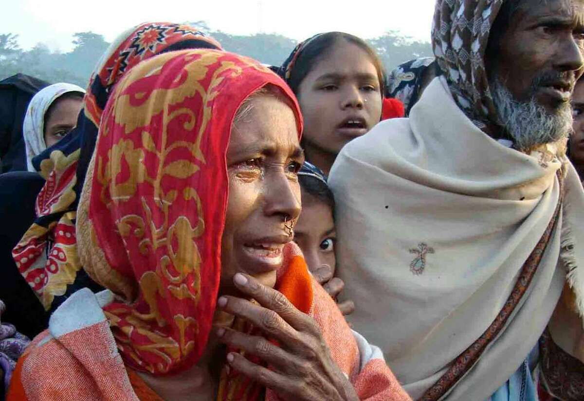 A woman weeps as she stands with others watching the triple-deck ferry, M.V. Coco, floating after it tipped and its rear portion sank in the Tetulia River late Friday near the coastal town of Bhola, 64 miles (104 kilometers) south of Dhaka, Bangladesh, Saturday, Nov. 28, 2009. The ferry packed with people going home for an Islamic festival capsized as they disembarked at a terminal in southern Bangladesh, authorities said Saturday. (AP Photo Firoz Ahmed)