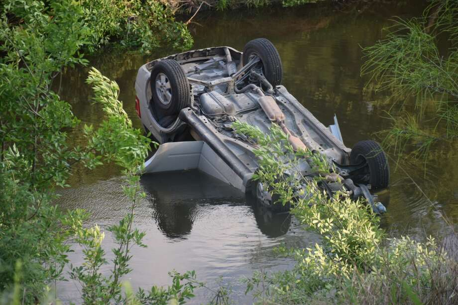 A driver rolled over an SUV into the Mission Reach portion of the San Antonio River on Wednesday, April 4, 2018. Photo: Caleb Downs / San Antonio Express-News
