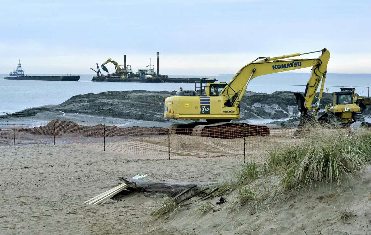 Madison, Connecticut - November 13, 2017: Tugboats, barges and excavating equipment at work during the Hammonasset State Park Beach Nourishment project on the state park's West Beach in Madison. Supervised by the Army Corp of Engineers the project that started this fall at the state's largest beach is scheduled to last until March 2018 in time for the 2018 summer season. 300,000 cubic yards of sand will be removed from the bottom of the Housatonic River, taken by barge 33 miles up the coast, and then pumped onto the western end of the Hammonasset Beach State Park which has been eroding, according to a November 6, 2016 New Haven Register article.