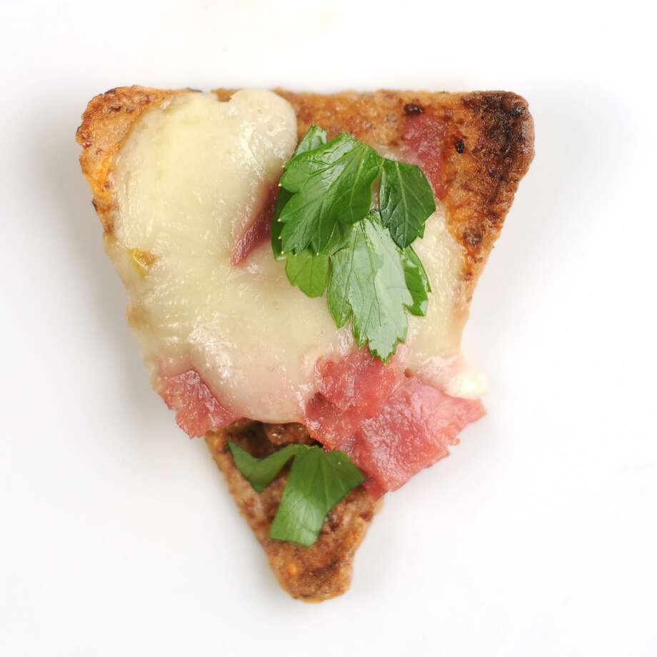 Italianacho topped with olive tapenade, provolone cheese, salami, ham and parsley. Photo: Paul Stephen /San Antonio Express-News