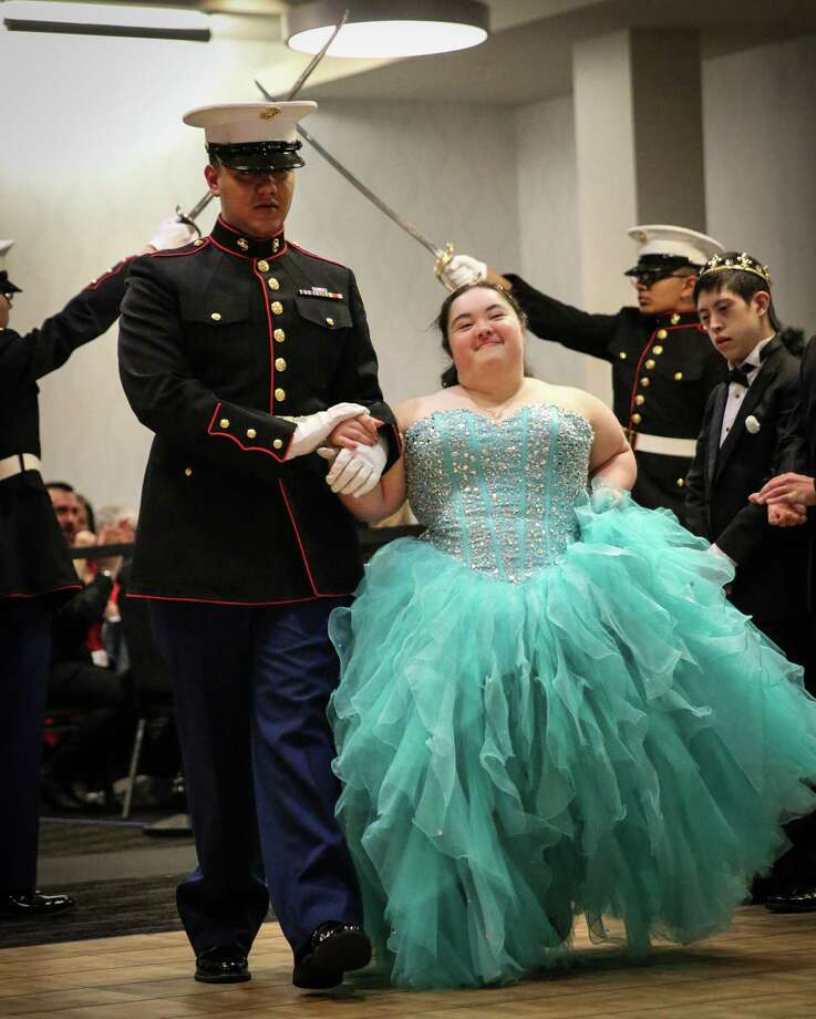 Gwendolyn Friedman of the Meyerland area is escorted into the Cinderella Ball by a cadet from the Tomball Memorial High School Marine Corps ROTC. Gwendolyn is a student at the Friends of Down Syndrome's Down Syndrome Academy. Photo: Fred Stewart