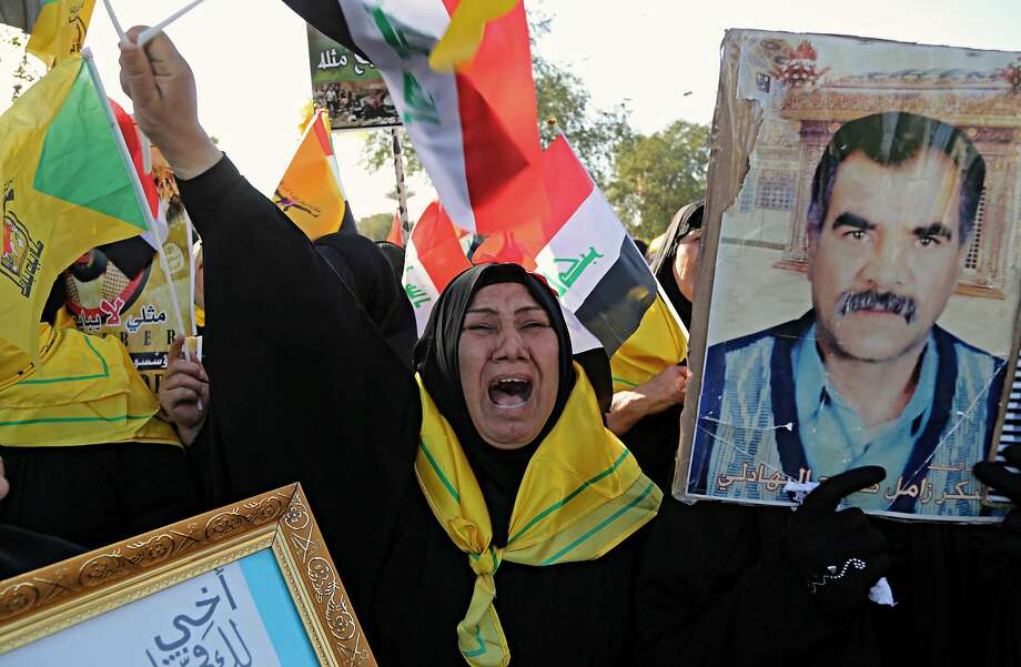 Iraqis carry a poster of a fighter who was killed, at a protest organized by the Iranian-backed Hezbollah brigades, that was active in the fight against Islamic State militants, in Baghdad, Iraq. Irans influence is looming large as Iraqis prepare to head to the polls for parliamentary elections in May, with many concerned that Tehran may be looking to strengthen its political grip on Baghdad in the vote. (AP Photo/Karim Kadim) Photo: Karim Kadim / Associated Press