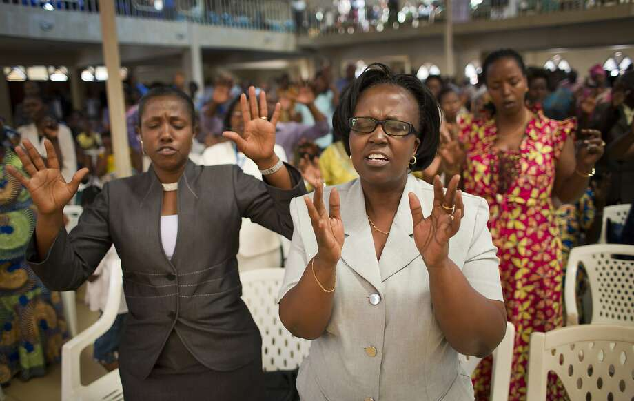 Rwandans sing and pray at the Evangelical Restoration Church in the capital, Kigali. The government says many churches have failed to comply with building safety standards. Photo: Ben Curtis / Associated Press