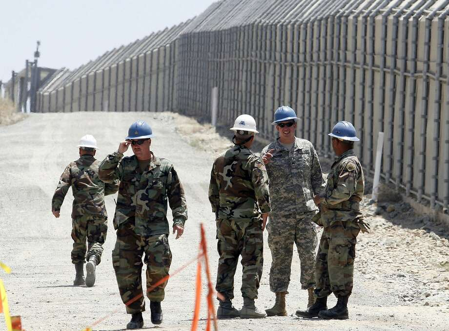 FILE - In this June 21, 2006, file photo, members of the California National Guard work next to the U.S.-Mexico border fence Wednesday, June 21, 2006, near the San Ysidro Port of Entry in San Diego. President Donald Trump said April 3, 2018, he wants to use the military to secure the U.S.-Mexico border until his promised border wall is built.  Photo: DENIS POROY / Associated Press