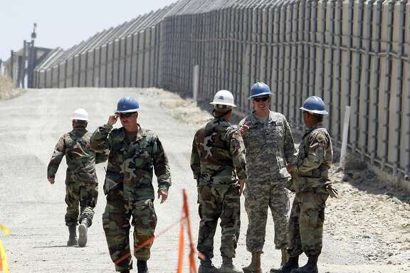FILE - In this June 21, 2006, file photo, members of the California National Guard work next to the U.S.-Mexico border fence Wednesday, June 21, 2006, near the San Ysidro Port of Entry in San Diego. President Donald Trump said April 3, 2018, he wants to use the military to secure the U.S.-Mexico border until his promised border wall is built. The Department of Homeland Security and White House did not immediately respond to requests for comment. At the Pentagon, officials were struggling to answer questions about the plan, including rudimentary details on whether it would involve National Guard members, as similar programs in the past have done. But officials appeared to be considering a model similar to a 2006 operation in which former President George W. Bush deployed National Guard troops to the southern border in an effort to increase security and surveillance.(AP Photo/Denis Poroy, File)
