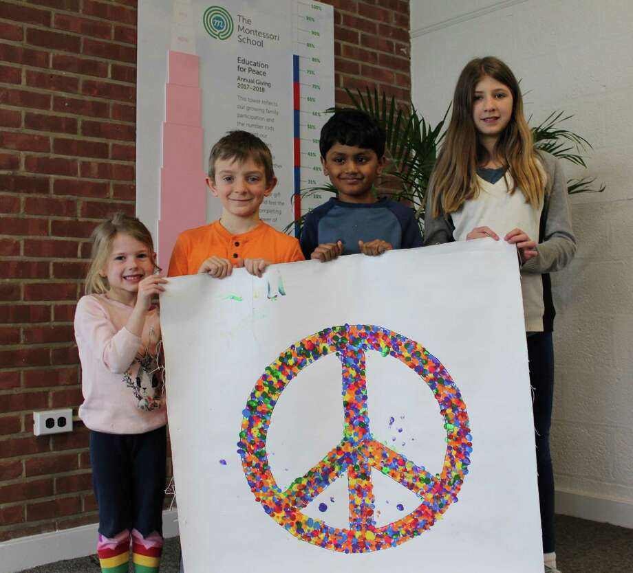 Montessori School students Hazel Samardzija, Quinn Dickinson, Tejes Prabhu and Laurel Aronian pose with a handmade 'peace flag' made by each school as a part of a new Save the Children program that connects students from all over the world. Photo: Pat Tomlinson / Hearst Connecticut Media
