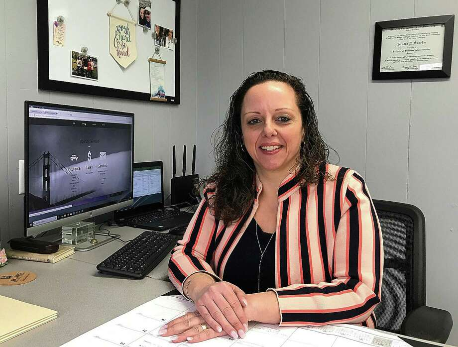Sandra Sanchez sits at her desk at Integrity Insurance, Taxes and Services -- a business she opened last month on South Street in Danbury, Conn. -- on WEdnesday, April 4, 2018. Photo: Chris Bosak / Hearst Connecticut Media / The News-Times