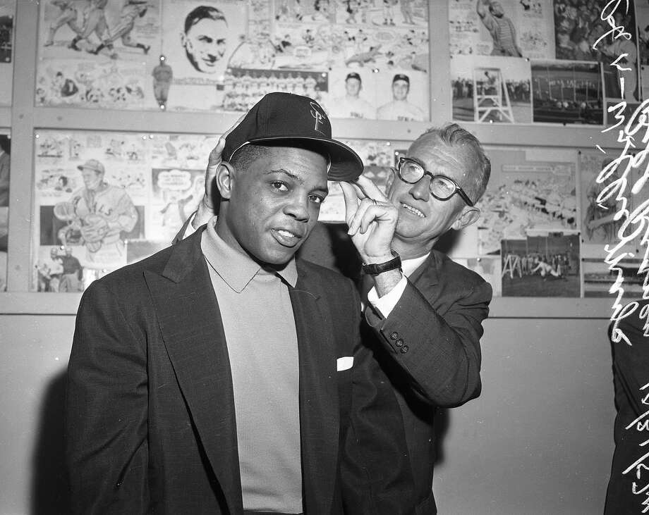 Willie Mays tries on a San Francisco Giants cap with the help of manager Bill Rigney on Oct. 31, 1957. Photo: Joe Rosenthal / The Chronicle 1957