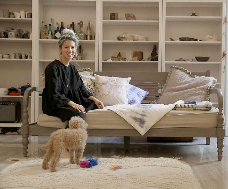 Designer Alexis Liu with her poodle, Noodle shows some of the fabrics she created for the couch at home on Monday, March 5, 2018, in San Francisco, Calif.