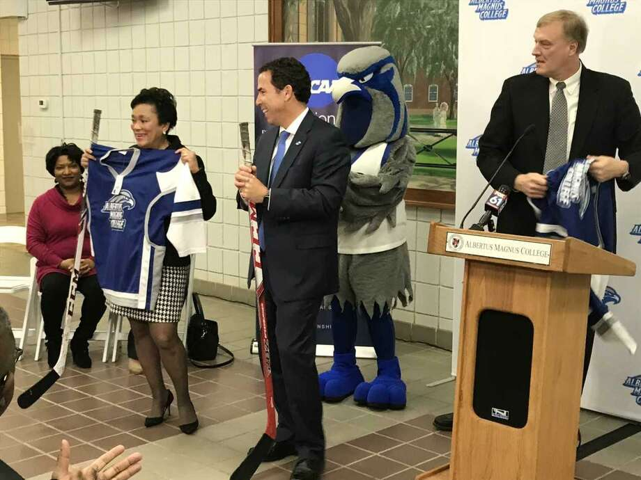 Mayor Toni Harp and Albertus Magnus College President Marc Camille receive personalized hockey jerseys as gifts. Photo: Brian Zahn / Hearst Connecticut Media