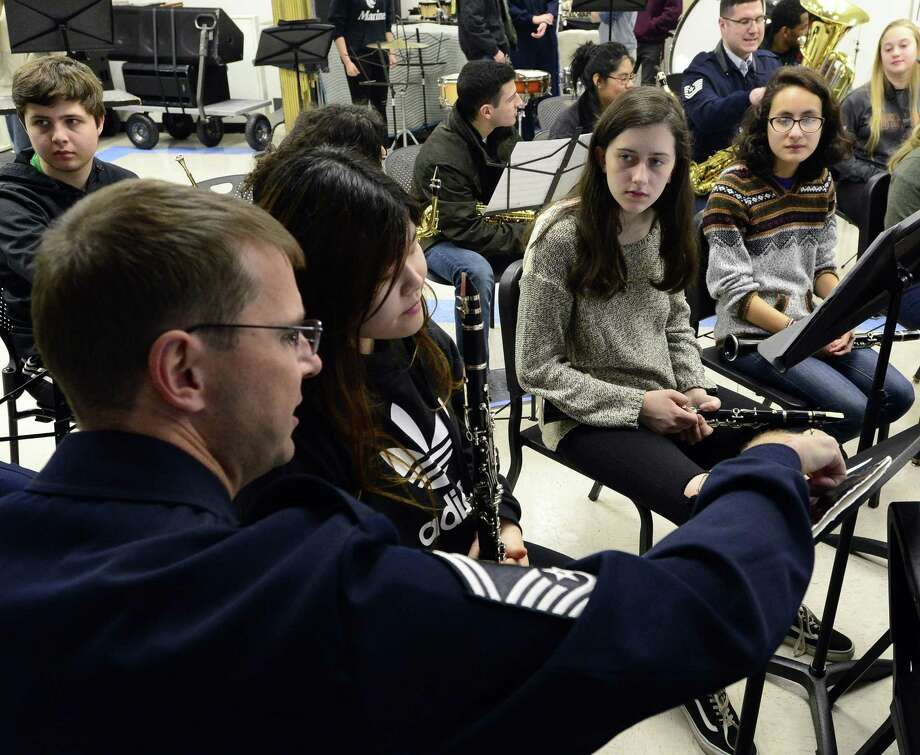 USAF SMStg Brian McCurdy of Virginia Beach, VA helps students Jessica Zheng of Stamford High School, Veronica Misiak and Rachel Brito, both of Westhill High School during a visit by members of the United States Air Force Band to a Master Class band rehersal on Tuesday, April 3, 2018 in Stamford, Connecticut. As part of Stamford Public Schools' chorale festival, brass, percussion and woodwind students from Westhill High School and Stamford High School will join the United States Air Force Concert Band on stage at The Palace Theatre performing marches and patriotic songs. Choral groups from both high schools will also join the Singing Sergeants in a choral selection for the finale. Photo: Matthew Brown / Hearst Connecticut Media / Stamford Advocate