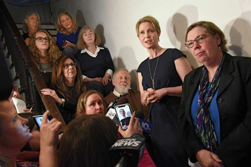 Gubernatorial candidate Cynthia Nixon, second from right, and former U.S. Environmental Protection Agency Regional Administrator Judith Enck, right, hold a news conference at the Delaney Hotel on Wednesday, April 5, 2018 in Hoosick Falls, N.Y. The two answered questions from residents, sitting on stairs at left, who were affected by their water supplies being polluted with a toxic manufacturing chemical four years ago. (Lori Van Buren/Times Union)