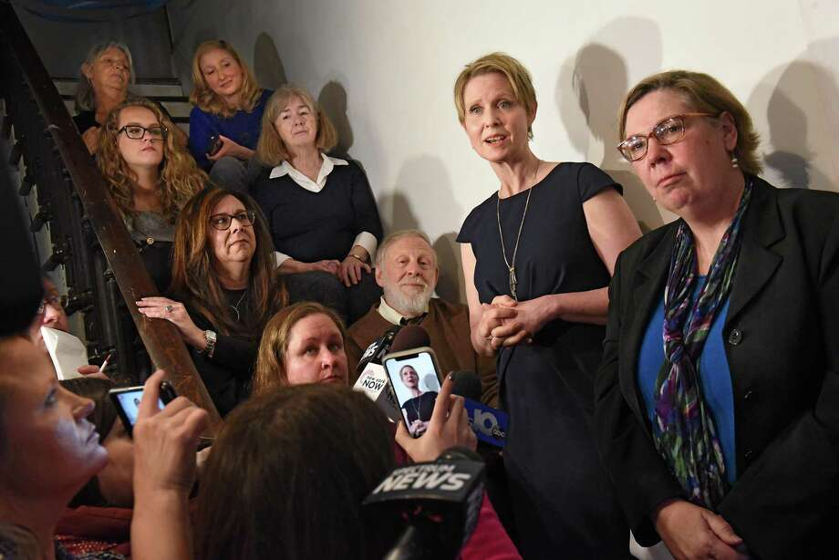 Gubernatorial candidate Cynthia Nixon, second from right,  and former U.S. Environmental Protection Agency Regional Administrator Judith Enck, right, hold a news conference at the Delaney Hotel on Wednesday, April 5, 2018 in Hoosick Falls, N.Y. The two answered questions from residents, sitting on stairs at left, who were affected by their water supplies being polluted with a toxic manufacturing chemical four years ago. (Lori Van Buren/Times Union) Photo: Lori Van Buren, Albany Times Union / 20043416A