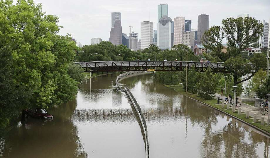 Onlookers at Buffalo Bayou checking out flooding on Monday, April 18, 2016, in Houston while a car sits adrift on the side of the road. ( Elizabeth Conley / Houston Chronicle ) Photo: Elizabeth Conley, Staff / Houston Chronicle / © 2016 Houston Chronicle