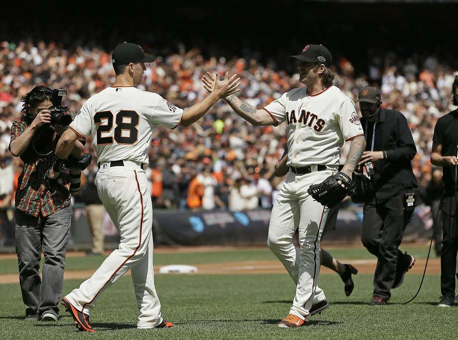 Former San Francisco Giants pitcher Brian Wilson, right, is greeted by catcher Buster Posey after throwing out a ceremonial first pitch before the start of an Opening Day baseball game between the Giants and the Seattle Mariners Tuesday, April 3, 2018, in San Francisco.  Photo: Eric Risberg / Associated Press