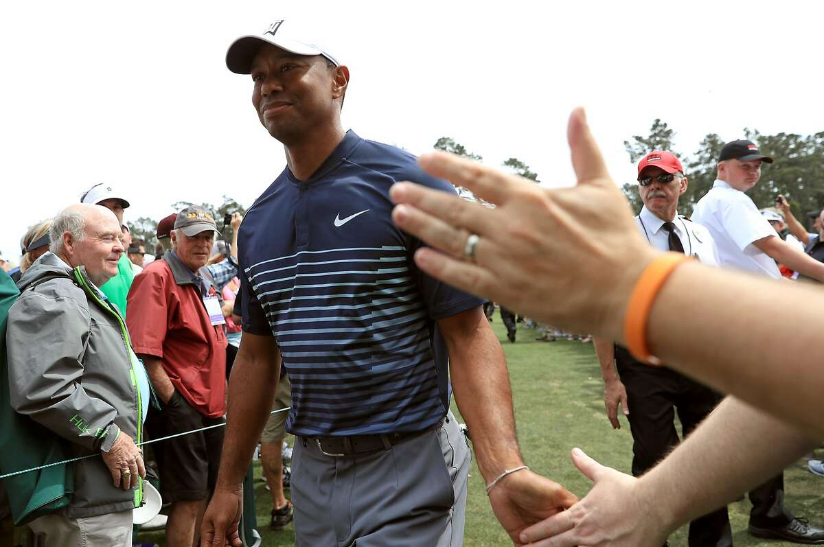 Tiger Woods of the United States shakes hands with patrons during a practice round prior to the start of the 2018 Masters Tournament at Augusta National Golf Club on April 4, 2018 in Augusta, Georgia.