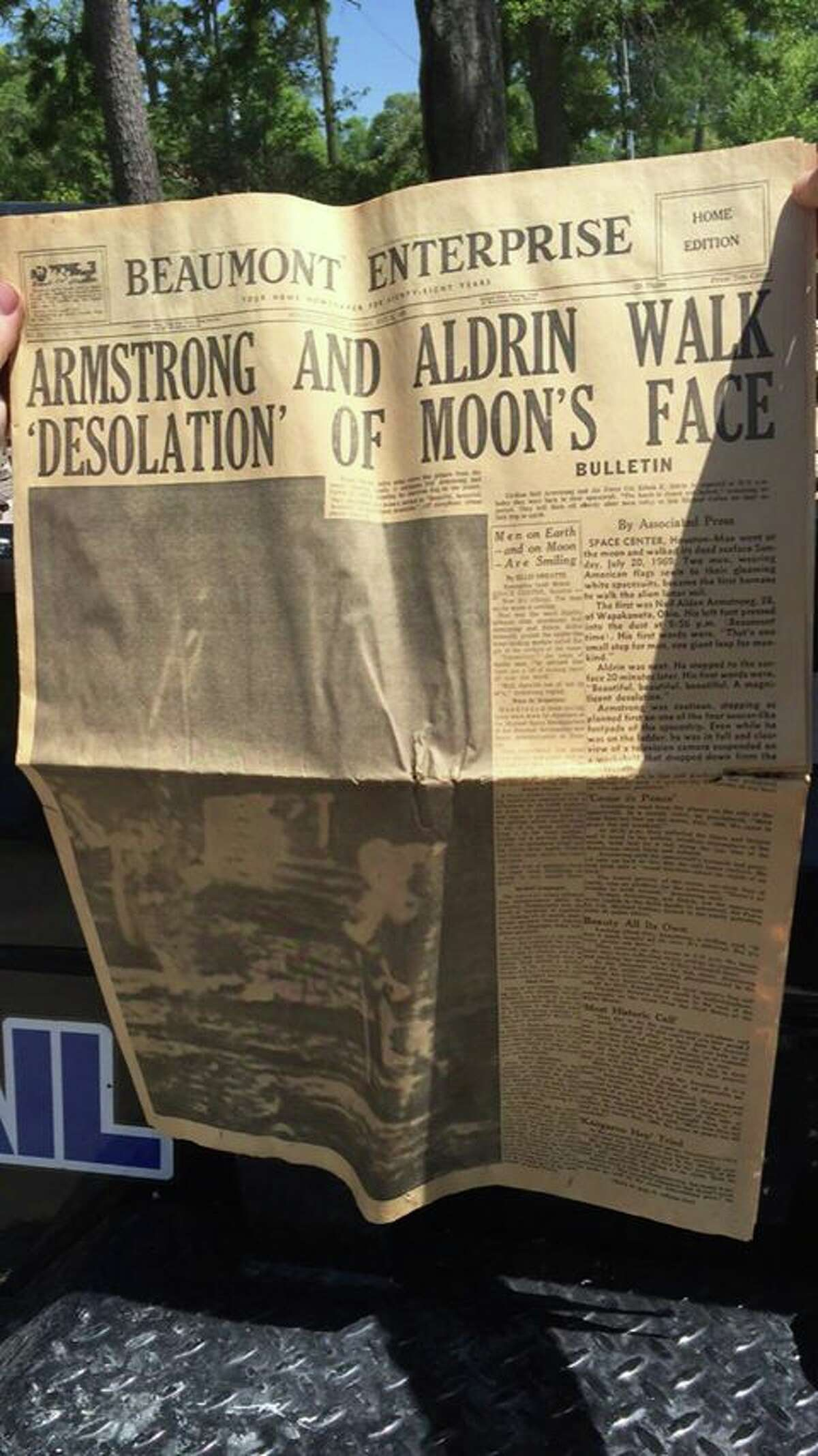 Dustyn Myatt, of Kirbyville, holds up a copy of the Beaumont Enterprise, dated July 21, 1969, reporting the news of astronauts Neil Armstrong and Edwin