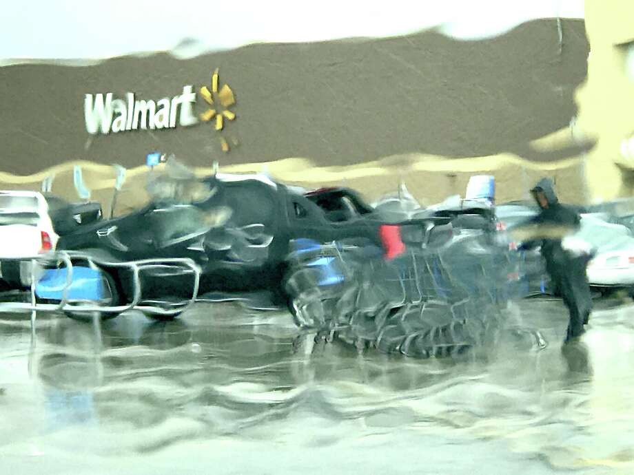 Seen through a rain-streaked windshield, a Walmart employee corrals carts in the lot of the chain's store in Port Arthur Sunday.   Photo taken Sunday, August 27, 2017 Kim Brent/The Enterprise Photo: Kim Brent / Beaumont Enterprise / BEN