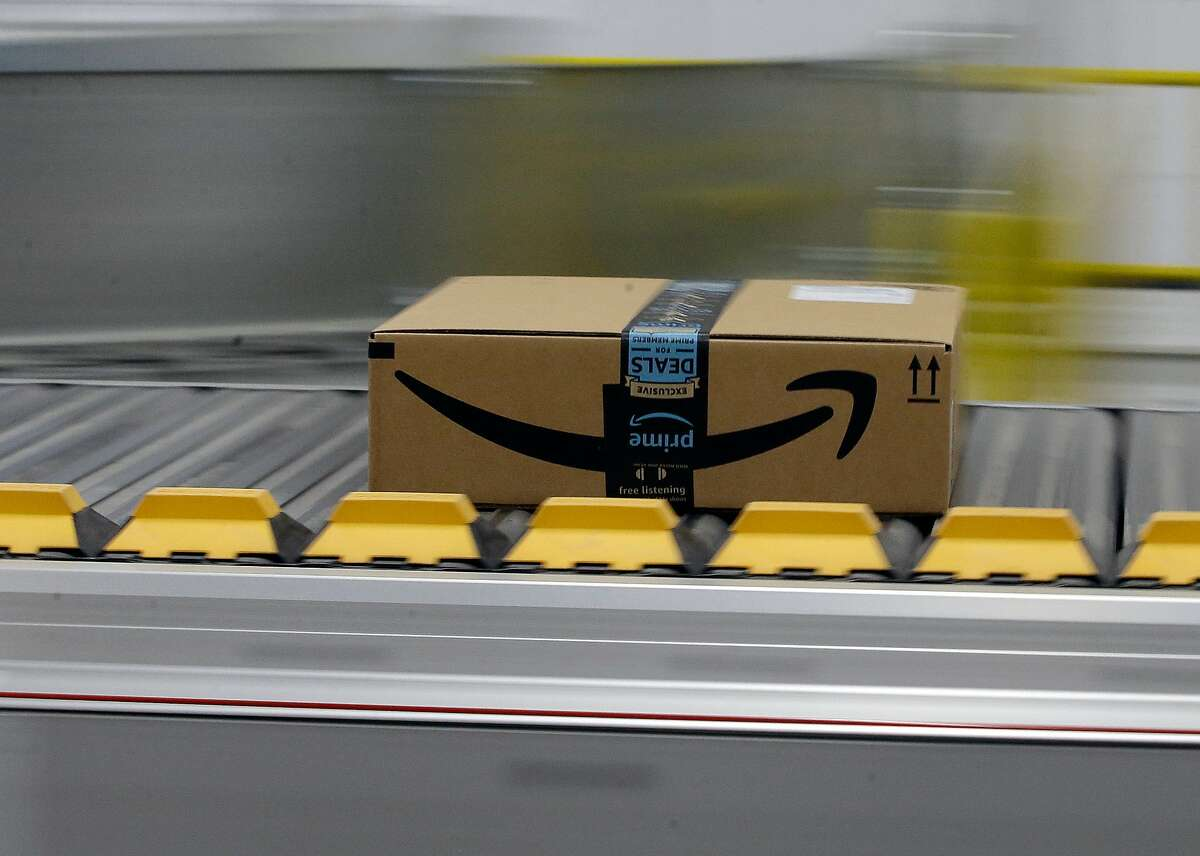 FILE- In this Feb. 9, 2018, file photo, a box for an Amazon prime customer moves through the new Amazon Fulfillment Center in Sacramento, Calif. This fulfillment center has been closed for nearly a week due to poor air quality in the region, resulting in a delay of packages to customers.