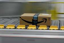 """FILE- In this Feb. 9, 2018, file photo, a box for an Amazon prime customer moves through the new Amazon Fulfillment Center in Sacramento, Calif. President Donald Trump took another shot at Amazon.com on Thursday, March 29, tweeting that the online retailer pays """"little or no taxes"""" and that it uses the U.S. Post Service as a """"Delivery Boy."""" (AP Photo/Rich Pedroncelli)"""