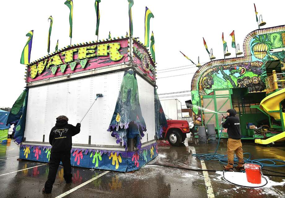 Jason Franceschi hoses down the Water Game while William Adams gives the game booth a good scrub Tuesday as Coleman Brothers Carnival opens for a 102nd season Thursday at Palmer Field in Middletown. The amusement park will be in town through April 14. Photo: Catherine Avalone / Hearst Connecticut Media / New Haven Register
