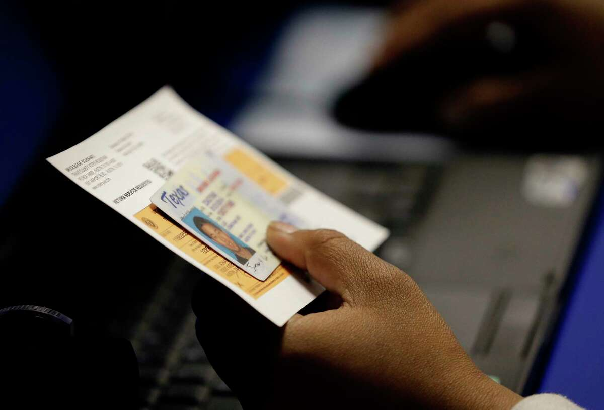 FILE - In this Feb. 26, 2014 file photo, an election official checks a voter's photo identification at an early voting polling site in Austin, Texas. A federal judge Wednesday, Aug. 23, 2017, again threw out Texas' voter ID requirements that she previously compared to a