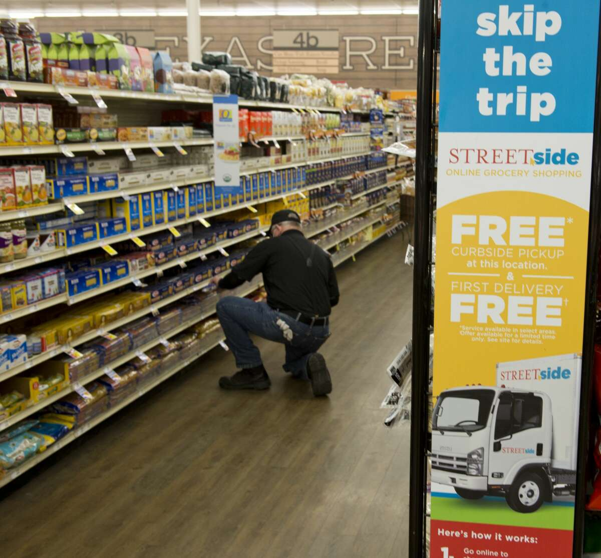 """Rick Barton finds groceries 02/28/18 at Market Street as he and other """"pickers"""" fill baskets with online orders for pickup or delivery as part of the Street Side groceries. Tim Fischer/Reporter-Telegram"""