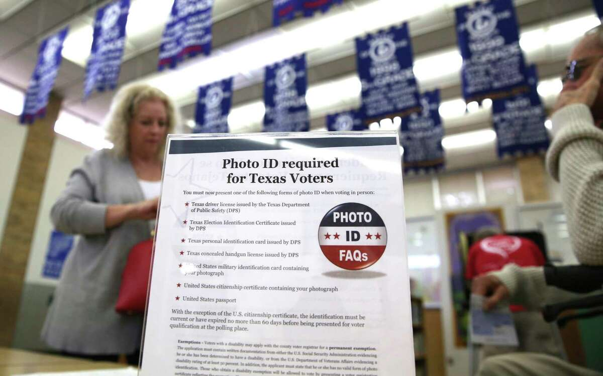 In this March 1, 2016, file photo, a sign tells voters of voter ID requirements before participating in the primary election at Sherrod Elementary school in Arlington, Texas. A Mexican national sentenced to eight years in prison for voter fraud in Texas says she was wrongly used by authorities as an example of fraud. Rosa Maria Ortega, who was brought to Texas as an infant, says she held a green card and always believed she was allowed to vote.