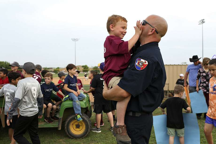Ryland Ward, 6, plays with Stockdale Assistant Fire Chief Rusty Duncan after Duncan threw out the first pitch for the Floresville High School baseball game at the school on Tuesday, April 3, 2018. Photo: Lisa Krantz / SAN ANTONIO EXPRESS-NEWS / SAN ANTONIO EXPRESS-NEWS