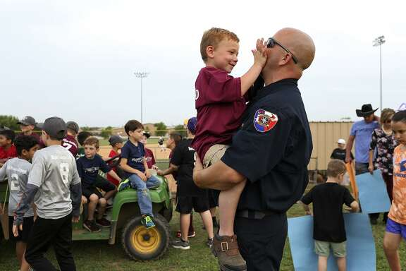Ryland Ward, 6, plays with Stockdale Assistant Fire Chief Rusty Duncan after Duncan threw out the first pitch for the Floresville High School baseball game at the school on Tuesday, April 3, 2018.
