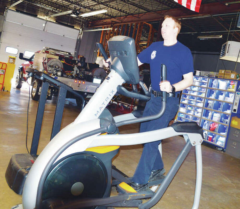 Firefighter Andrew Mitchell works out on an elliptical in a Godfrey firehouse as part of the health-and-wellness program, recently instituted by the Godfrey Fire Protection District and administered by Drs. Jacob and Katie Drake Sherer. Photo: Vicki Bennington|For The Telegraph