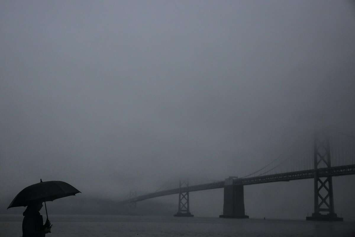 Jorge Venegas stops to look at the Bay Bridge during a rainstorm in San Francisco, Calif., on Monday, Jan. 8, 2018.