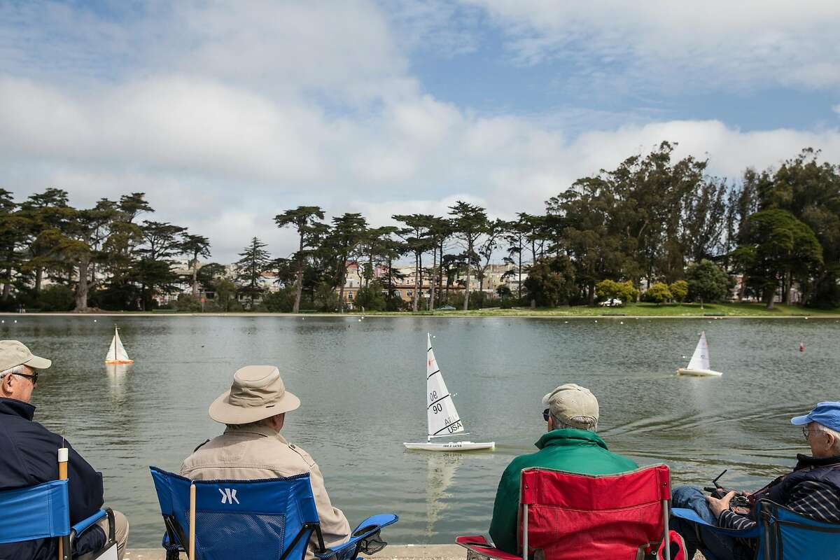 (From left) Til Mossi of San Francisco, Larry Cumeo of San Francisco, Bob Pearsall of Millbrae and Micahel Fischer of Mill Valley enjoy the weather while steering their model ships at Spreckles Lake in Golden Gate Park Wednesday, April 4, 2018 in San Francisco, Calif. before a large rainstorm is expected to drench the Bay Area Thursday.