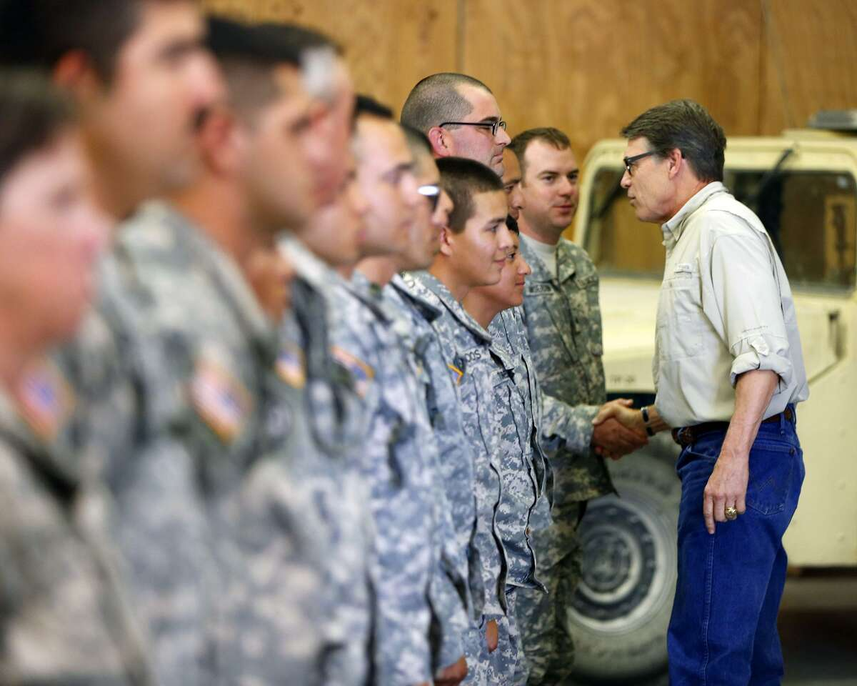 Then-Texas Gov. Rick Perry shakes hands with National Guard troops training at Camp Swift in Bastrop, near Austin, in this Aug. 13, 2014 file photo. President Donald Trump's announcement Tuesday, April 3, 2018, that he wants to use the military to secure the U.S.-Mexico border echoes the response of Texas leaders during a surge of Central American children crossing the Rio Grande four years ago. Perry, who is now Energy Secretary under Trump, ordered the Texas National Guard to deploy along the Rio Grande in July 2014. (William Luther/The San Antonio Express-News via AP, File)
