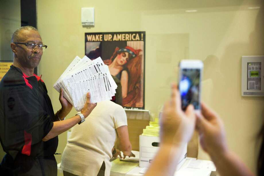 San Antonio, Texas -- October 11, 2016 -- John Owens of the San Antonio branch of the NAACP holds up voter registration forms that he turned in at the Bexar Country Elections Office. Ray Whitehouse / for the San Antonio Express-News Photo: Ray Whitehouse, Photographer / For The San Antonio Express-News