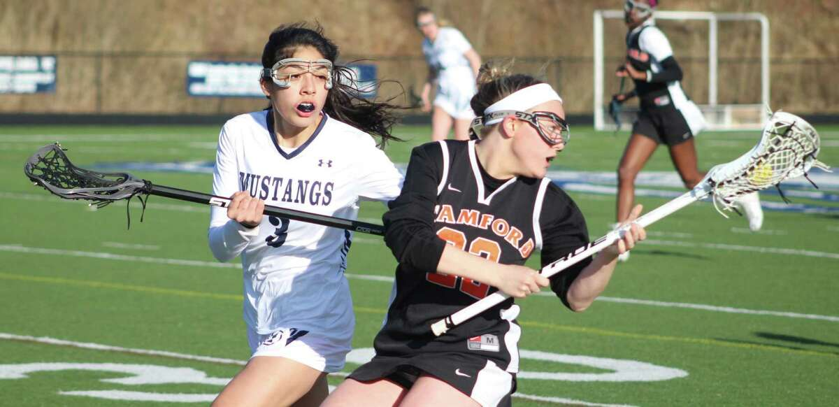 Stamford's Olivia LaBella, right, controls the ball as Immaculate's Kasey Peralta defends during the girls lacrosse game at Immaculate High School in Danbury April 4, 2018.