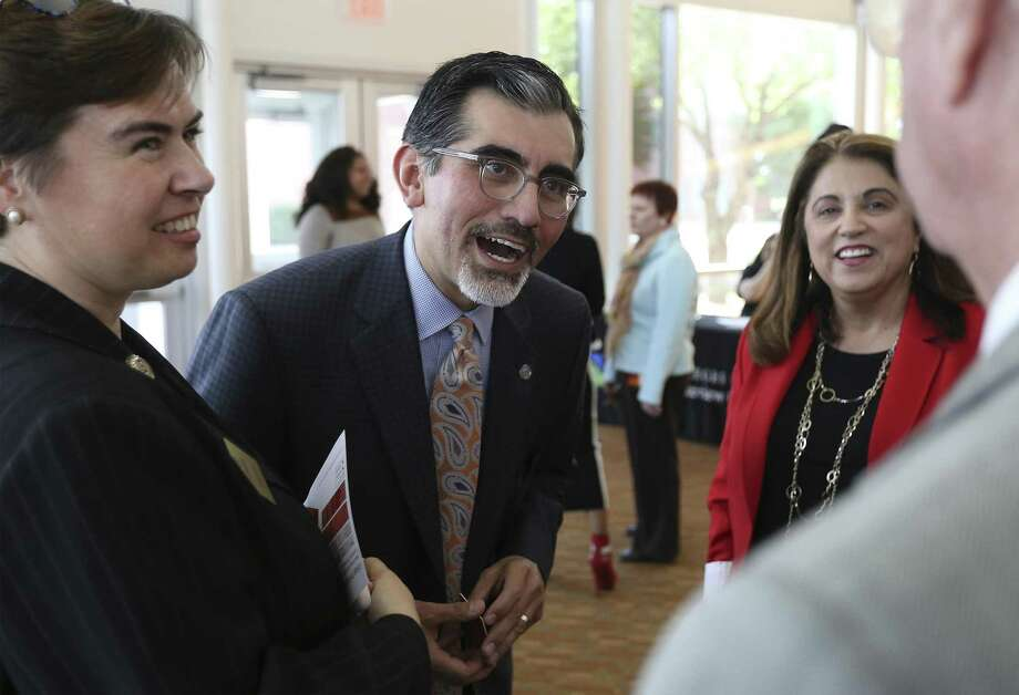 The incoming chancellor of the Alamo Colleges, Mike Flores (center), chats with guests Wednesday during a meet-and-greet at Northeast Lakeview College. Photo: Kin Man Hui /San Antonio Express-News / ©2018 San Antonio Express-News