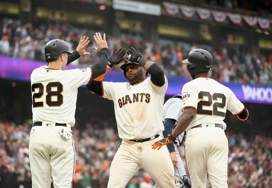 Buster Posey and Andrew McCutchen congratulate Pablo Sandoval of the San Francisco Giants after he ht a three-run home run in the fifth inning against the Seattle Mariners at AT&T Park on April 4, 2018 in San Francisco, California.  Photo: Ezra Shaw / Getty Images