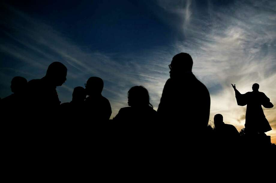 A statue of Rev. Martin Luther King Jr. is silhouetted against the evening sky as people attend the Black Heritage Society's 50th annual Candlelight Vigil at MacGregor Park Wednesday, April 4, 2018 in Houston. Photo: Michael Ciaglo, Houston Chronicle / Michael Ciaglo
