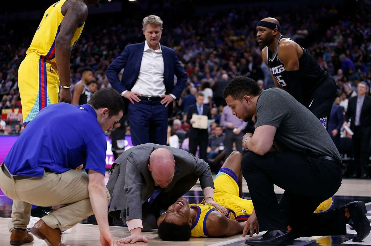 Warriors guard Patrick McCaw is attended to by Golden State's medical staff after he was fouled by the Kings' Vince Carter, landed on the hardwood, writhing in pain, and was taken off the court on a stretcher.