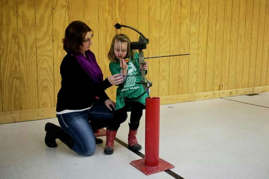 In this Daily News file photo, Olivia Paisley, 4, of Midland, is supervised by her mother, Kelli, during the final night of the Mid-Michee Bowmen Winter League youth shoot in Midland. / Midland Daily News