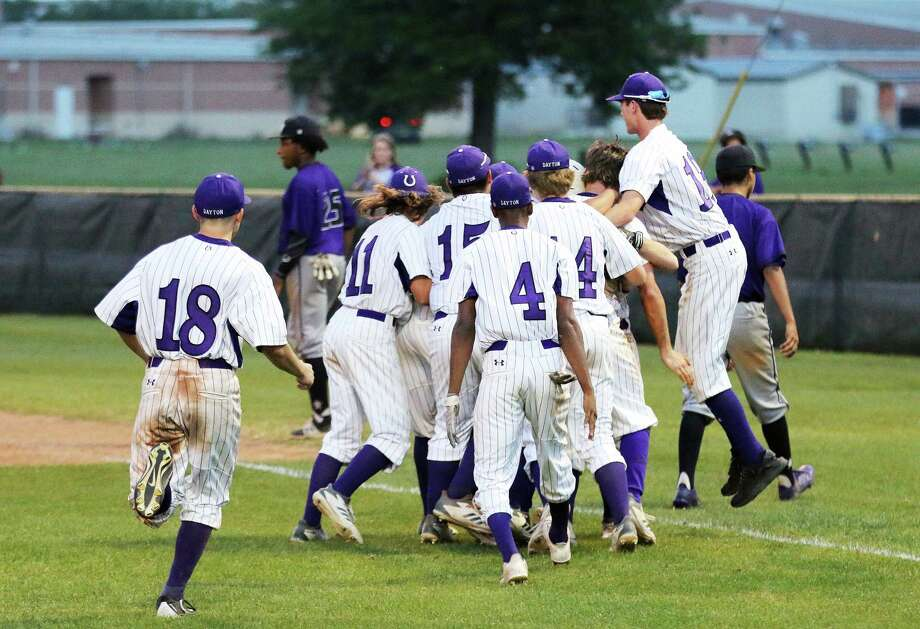 Freshman Matt Drabbant is mobbed at first base by his teammates after he hit a walk-off single to end the 10 inning game, 6-5, for the Broncos. The win keeps the Broncos in the hunt for a district title and playoff spot. Photo: David Taylor