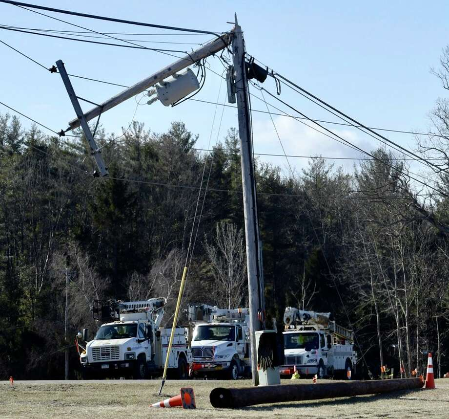 National Grid and Verizon company crews arrive Thursday to repair snapped utility poles near the Saratoga County Sheriff's Office in Ballston Spa. High winds swept through the area Wednesday night and Thursday morning, downing powerlines, trees and branches around the region. Photo: Skip Dickstein / Times Union