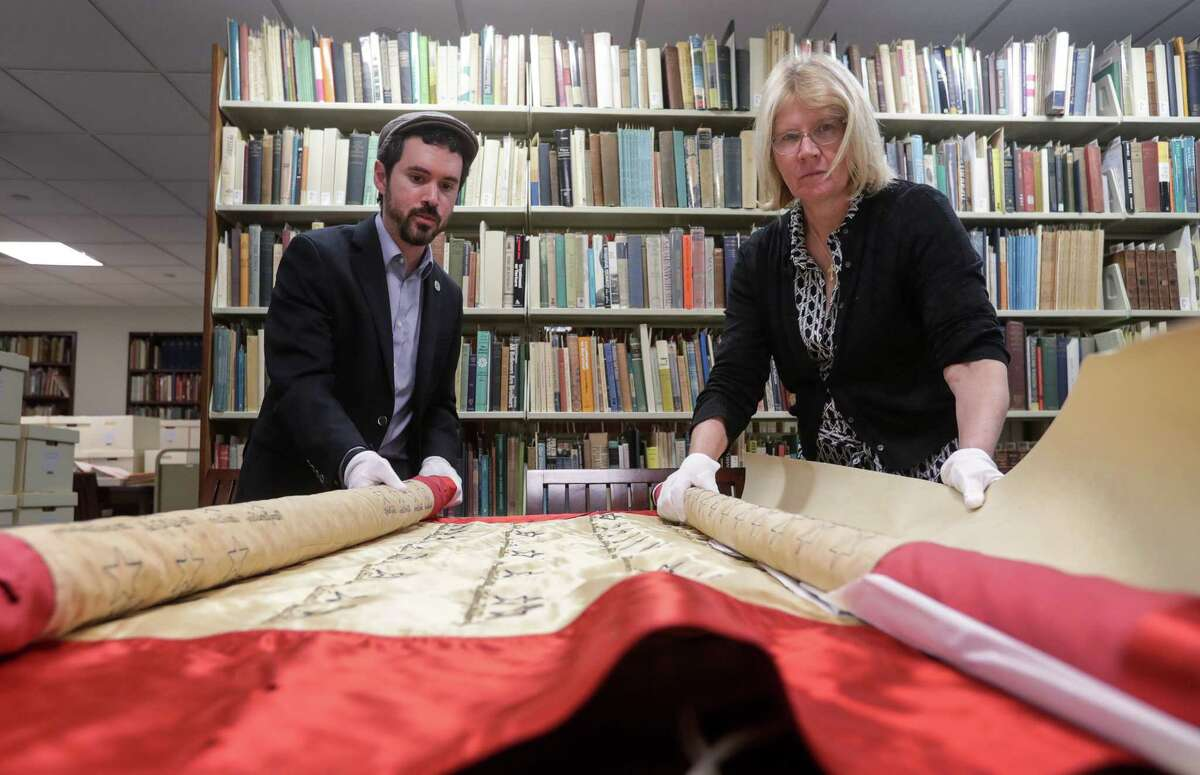 Joshua Furman, a postdoctoral fellow in Jewish studies, and Melissa Kean, a historian at Rice University, show a World War II-era banner from Beth Jacob Congregation that will be serve as the centerpiece of Rice's new Houston Jewish History Archive.