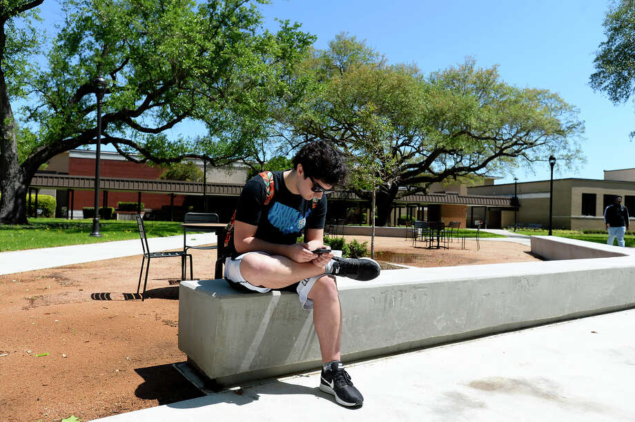 Brayden Baker looks at his phone while passing time between classes in the quad at Lamar University. The area was reopened this semester after being fully renovated.  Photo taken Wednesday 4/4/18 Ryan Pelham/The Enterprise Photo: Ryan Pelham / ©2017 The Beaumont Enterprise/Ryan Pelham