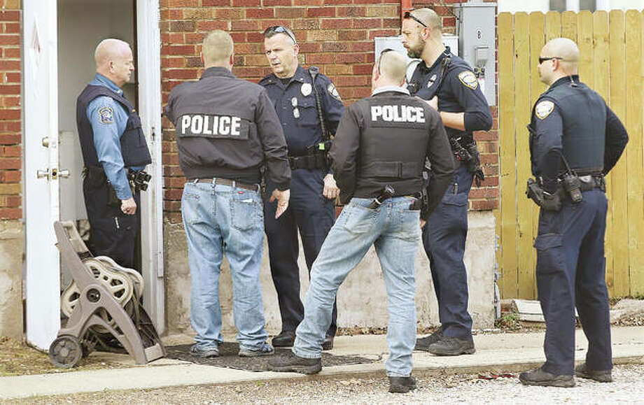 East Alton Police Chief Darren Carlton, left, and Wood River Police Chief Brad Wells, center, talk with officers outside the house they raided on a warrant last month in the 300 block of Bowman, East Alton. Another raid, executed jointly by Wood River and East Alton, took place before dawn Thursday, resulting in five people being taken in for questioning. Photo: John Badman | The Telegraph