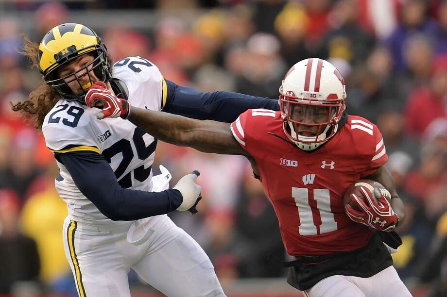 MADISON, WI - NOVEMBER 18:  Nick Nelson #11 of the Wisconsin Badgers avoids a tackle by Jordan Glasgow #29 of the Michigan Wolverines during a game at Camp Randall Stadium on November 18, 2017 in Madison, Wisconsin.  Wisconsin defeated Michigan 24-10.  (Photo by Stacy Revere/Getty Images) Photo: Stacy Revere/Getty Images