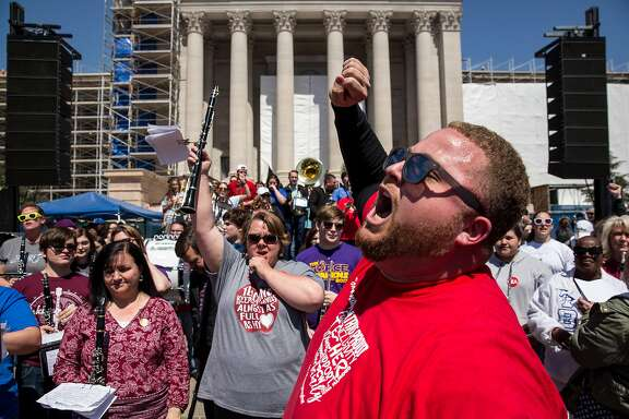 OKLAHOMA CITY, OK - APRIL 04: Putnam City West band director Edward Hudson leads the The Oklahoma Teacher Walkout Band, an improvised group of music teachers from across the state, in a pep rally on the steps of the state Capitol on April 4, 2018 in Oklahoma City, Oklahoma. Teachers and their supporters are demanding increased school funding and pay raises for school workers. (Photo by Scott Heins/Getty Images)
