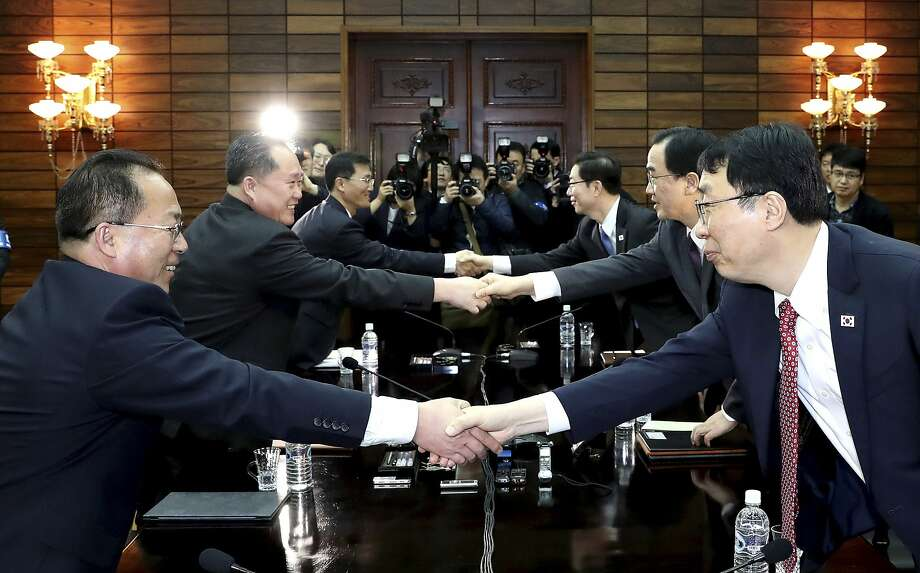 South Korean diplomats (right) shake hands with their North Korean counterparts at the border village of Panmunjom. They discussed security, protocol and media coverage issues. Photo: Associated Press
